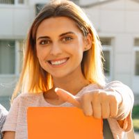 Happy two young students with note-books and backpacks smiling and showing thumb up  while standing on background of university and friends